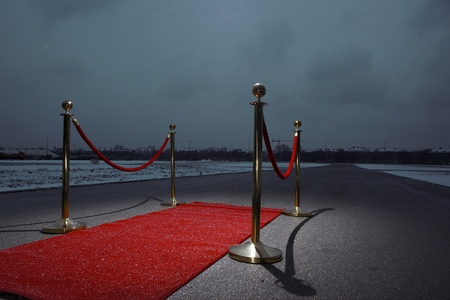 Red carpet on street, city in the background, dark clouds LANG_EVOIMAGES