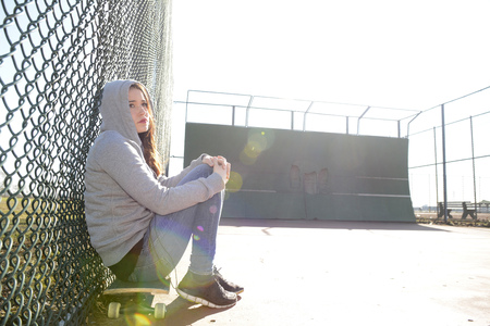 Sad woman sitting on her skateboard on a sports field LANG_EVOIMAGES