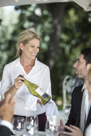 well laid: Waitress showing white wine to clients at table