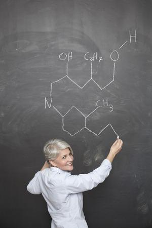 formulae: Mature teacher drawing chemical formula on blackboard LANG_EVOIMAGES