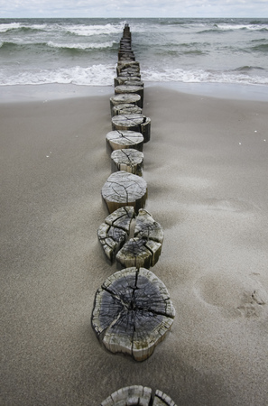 stormy waters: Germany, Fischland Darss Zingst, wooden stakes on the beach LANG_EVOIMAGES