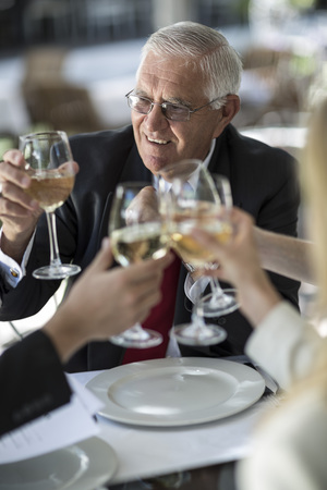 well laid: People at outside restaurant clinking white wine glasses