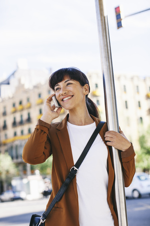 Spain, Barcelona, portrait of smiling businesswoman telephoning with smartphone at the bus stop