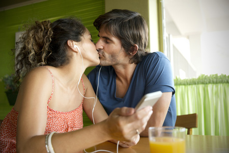 africa kiss: Couple in a cafe kissing and listening to music