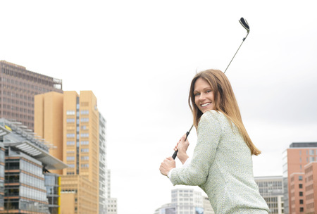 motivations: Germany, Berlin, Young businesswoman playing golf