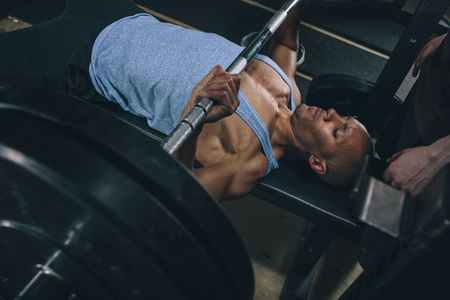 motivations: Young man exercising bench press in gym