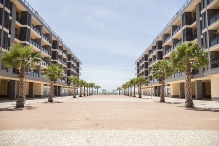conformance: Portugal, Olhao, two apartment buildings with palms in front