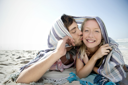 africa kiss: Happy young couple lying on beach kissing under a blanket