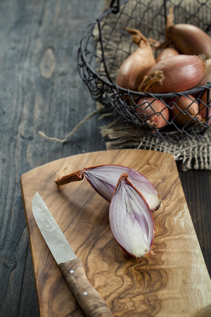 close up of onions in a basket: Sliced shallot on wooden board LANG_EVOIMAGES