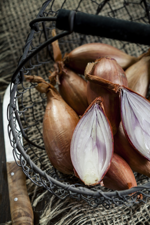 close up of onions in a basket: Sliced and whole shallots in a wire basket LANG_EVOIMAGES