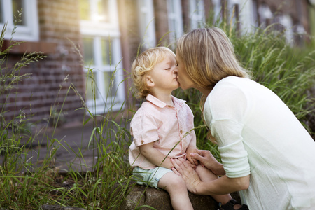 Mother kissing her little son in front of the house