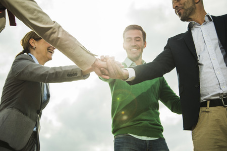 motivations: Four happy businesspeople stacking their hands outdoors LANG_EVOIMAGES