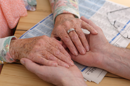 evening newspaper: Hands of senior woman holding mans hands