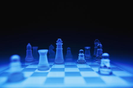 Chess pieces on blue glass board against dark background