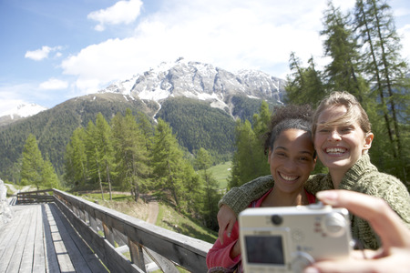 mountaintops: Switzerland, two happy women taking a selfie with camera LANG_EVOIMAGES