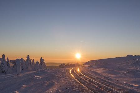 narrow gauge railroad: Germany, Saxony-Anhalt, Harz National Park, Brocken, rail tracks of Harz Narrow Gauge Railway in winter against the evening sun