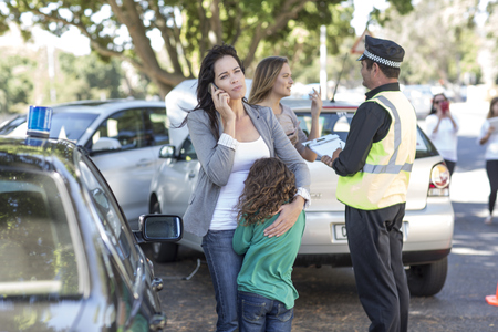 collisions: People and policeman at car accident scene