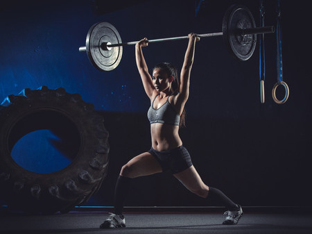 motivations: CrossFit athlete at weight training looking with barbell