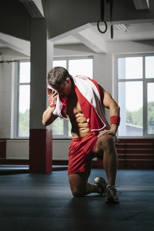 motivations: Man wiping off sweat after Goup Fitness training