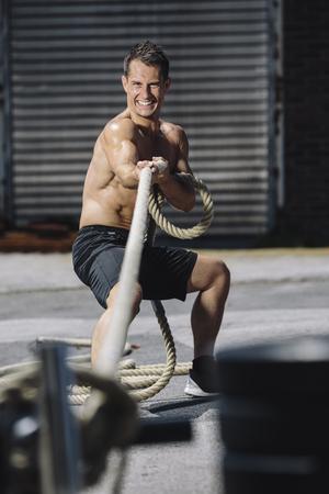 motivations: CrossFit athlete pulling rope LANG_EVOIMAGES