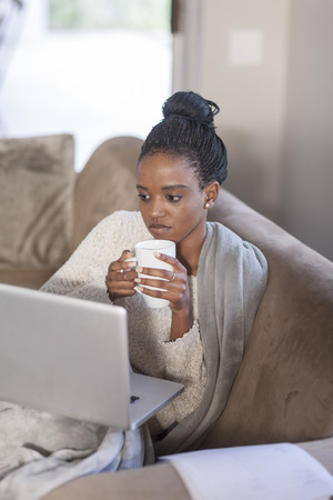 Young woman with laptop drinking coffee at home LANG_EVOIMAGES