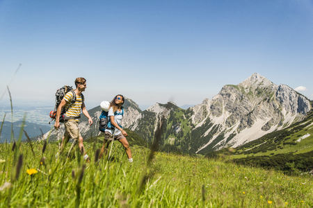 mountaintops: Austria, Tyrol, Tannheimer Tal, young couple hiking on alpine meadow