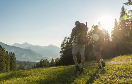mountaintops: Austria, Tyrol, Tannheimer Tal, young couple hiking on alpine meadow in backlight