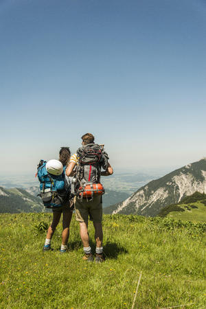 mountaintops: Austria, Tyrol, Tannheimer Tal, young couple standing on alpine meadow looking at view LANG_EVOIMAGES