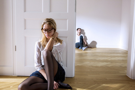 Pensive young woman in empty apartment with man in background LANG_EVOIMAGES