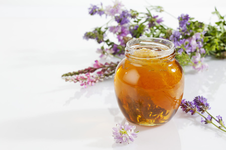 red clover: Glass of blossom honey with honeycomb and blossoms on white ground
