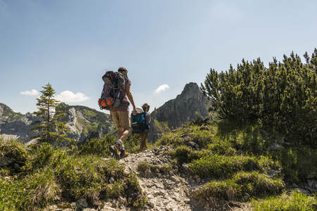 mountaintops: Austria, Tyrol, Tannheimer Tal, young couple hiking on mountain trail LANG_EVOIMAGES