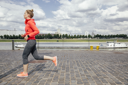 motivations: Germany, Cologne, young woman jogging at River Rhine LANG_EVOIMAGES