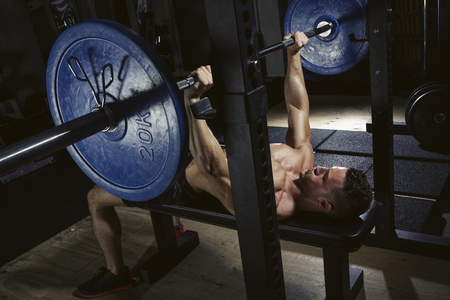 motivations: Physical athlete doing barbell bench presses LANG_EVOIMAGES