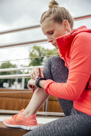 self testing: Young sporty woman checking her smart watch