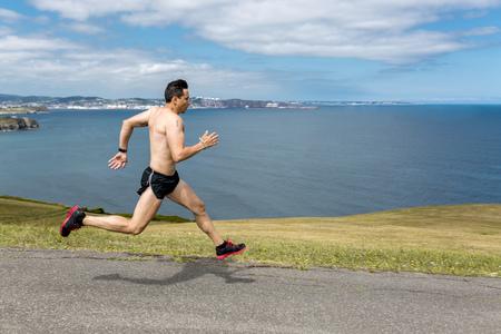motivations: Shirtless man jogging at the coast