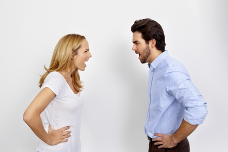 lovers quarrel: Angry couple shouting at each other in front of white background