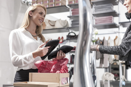 selling service: Shop assistant and customer in a shoe shop LANG_EVOIMAGES