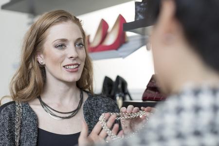 Shop assistant advising woman in a boutique
