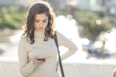 Young woman with cellphone in city
