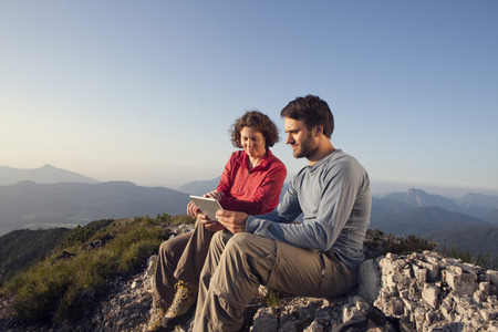 Austria, Tyrol, Unterberghorn, two hikers sitting with digital tablet in alpine landscape