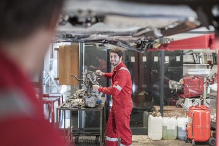 Car mechanics at work in repair garage