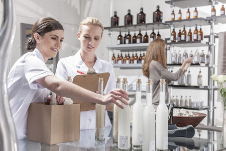 selling service: Two shop assistants in wellness shop packing bottles