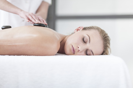 lastone therapy: Woman receiving hot stone massage in a spa LANG_EVOIMAGES