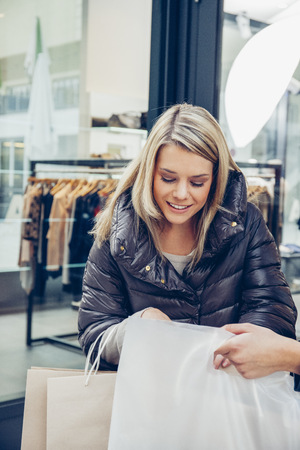 Young woman outside a boutique looking in shopping bag