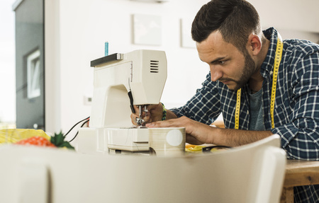 Young man at home using sewing machine LANG_EVOIMAGES