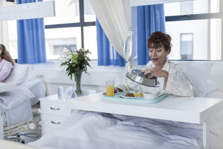 Content patient in hospital bed having lunch LANG_EVOIMAGES
