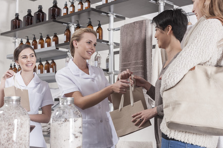 selling service: Shop assistant in wellness shop handing over bag to client LANG_EVOIMAGES