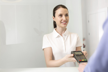 Young woman at the reception handing over credit card reader