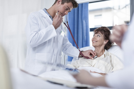 Doctor examining woman in hospital bed LANG_EVOIMAGES