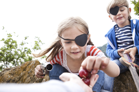 mujer pirata: Boy and girl dressed up as pirates receiving cherries LANG_EVOIMAGES